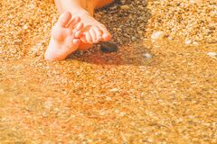 Vacation and holidays concept. Close up feet of young girl relaxing on beach and enjoying sea on sunny summer day