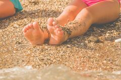Vacation and holidays concept. Close up feet of young girl relaxing on beach enjoying sun and sea on sunny summer day. Horizontal