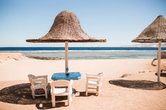 Vacation holidays. three beach lounge chairs under tent on beach. Royalty Free Stock Image