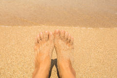 Vacation holidays. Woman feet closeup of girl relaxing on beach Stock Photos