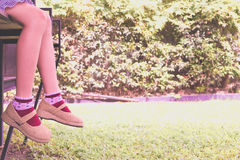 Vacation holidays. Woman feet closeup of girl relaxing on bench. In garden.soft focus. vintage filter effect Stock Photography