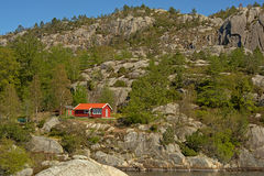 Vacation house on a rocky mountain slope with trees Stock Image