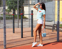 Vacation. Incredible tanned long-legged brunette in white shorts, a turquoise shirt and fashionable white sneakers Stock Photo