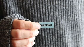 Vacation - inscription on the tag. The guy holds a tag with the text in his hand stock video footage