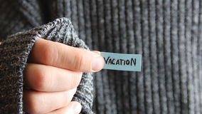 Vacation - inscription on the tag. The guy holds a tag with the text in his hand stock footage