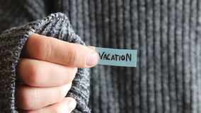 Vacation - inscription on the tag. The guy holds a tag with the text in his hand stock video