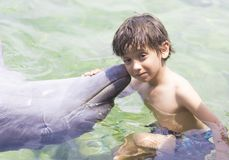 Vacation Lifestyle -Happy Boy hugging a dolphin. Summertime, Vacation Lifestyle -Happy Boy hugging and kissing a dolphin stock photo