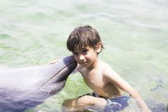Vacation Lifestyle -Happy Boy hugging a dolphin. Summertime, Vacation Lifestyle -Happy Boy hugging and kissing a dolphin royalty free stock photos