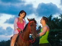Vacation Lifestyles-Couple Horseback Riding at Royalty Free Stock Images