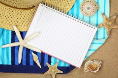 Vacation memory from beach. Notebook,starfish,straw hat and towel on sand beach Stock Image