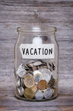 Vacation, money jar with coins on wood table Stock Images