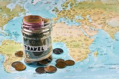 Travel budget concept, close-up. Vacation money savings in a glass jar with travel text . World map background. Travel budget concept, close-up Royalty Free Stock Images