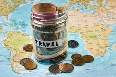 Travel budget concept, close-up. Vacation money savings in a glass jar with travel text . World map background. Travel budget concept, close-up Stock Images