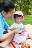 Vacation, mother and little asian girl enjoy eating their lunch Stock Images