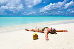 Vacation paradise in the Caribbean. Young woman lying on the beach Girl with coconut on white sand by the tropical turquoise waters of the Caribbean to Hawaii Stock Image