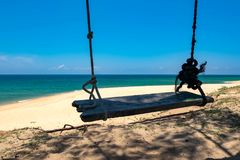 wooden swing over beautiful tropical beach, soft wave hitting sandy beach under bright sunny day. Royalty Free Stock Photography