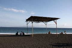 Vacation photo - Beach with black sand in Bali, sea, shed. Vacation photo - Beach with black sand in Bali, sea, shed, island far away, some people on the beach Royalty Free Stock Photos