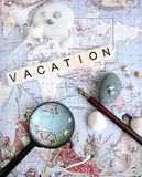 Vacation planning concept. A conceptual photograph of the word vacation, placed on an antique world map, and taken with old calligraphy pen, sea shells, pebbles