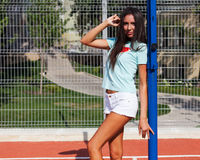 Vacation. Portrait, close-up of a tanned long-legged brunette in white shorts, a turquoise shirt posing on a basketball Royalty Free Stock Photo