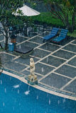 Vacation rain. Tourist resort pool under tropical rain Royalty Free Stock Image