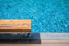 Vacation and Relaxation Concept : Wooden long chair beside swimming pool in the resort. Royalty Free Stock Photo