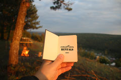 Vacation rentals, book with text. Sunset, forest. Stock Photos