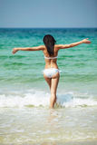 Vacation & resort. Happy beautiful woman model with perfect body. Happy woman in white bikini swimwear open her heart to sun. Vacation, beautiful sea and Royalty Free Stock Photography