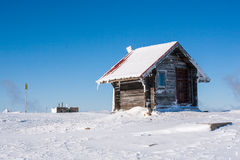 Vacation rural winter background. Small wooden alpine house covered with snow Stock Photos