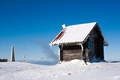 Vacation rural winter background. Small wooden alpine house covered with snow Royalty Free Stock Photos