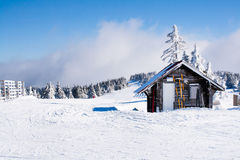 Vacation rural winter background. Small wooden alpine house covered with snow Royalty Free Stock Images