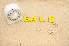 Vacation Sale Time. A white timer and the word sale sitting on a beach with starfish, vacation sale time Royalty Free Stock Photo