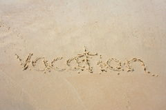 Vacation in the sand. Vacation written in the sand stock image