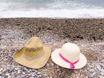 Vacation on the sea. Two straw hats lay on a beach on seacoast Stock Image