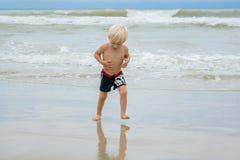 A happy blond boy child walking in water at a sea shore beach, Nha Trang, Vietnam stock photos
