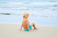 A thoughtful blond boy child sits near water at a sea shore beach, Nha Trang, Vietnam Royalty Free Stock Image
