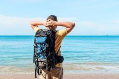 Vacation with a sea view - a tourist with a backpack. Admires the sea Stock Images