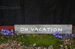 On vacation sign by blue flowers Royalty Free Stock Photography