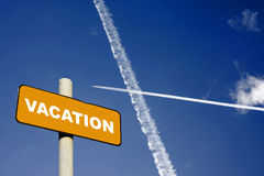 Vacation sign with jet trails in a dark blue sky Royalty Free Stock Photo