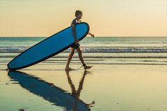 Vacation Silhouette Of A Surfer Carrying His Surf Board Home At Sunset With Copy Space.  Royalty Free Stock Image