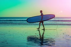 Vacation Silhouette Of A Surfer Carrying His Surf Board Home At Sunset With Copy Space.  Royalty Free Stock Images