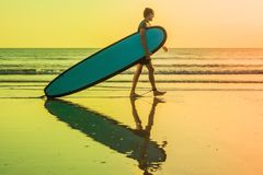 Vacation Silhouette Of A Surfer Carrying His Surf Board Home At. Sunset With Copy Space Stock Photos