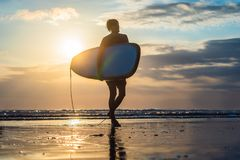 Vacation Silhouette Of A Surfer Carrying His Surf Board Home At. Sunset With Copy Space Stock Photo