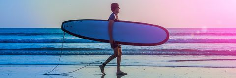 Vacation Silhouette Of A Surfer Carrying His Surf Board Home At Sunset With Copy Space BANNER, long format. Vacation Silhouette Of A Surfer Carrying His Surf Stock Images