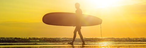 Vacation Silhouette Of A Surfer Carrying His Surf Board Home At Sunset With Copy Space BANNER, long format. Vacation Silhouette Of A Surfer Carrying His Surf Royalty Free Stock Photography