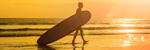 Vacation Silhouette Of A Surfer Carrying His Surf Board Home At Sunset With Copy Space BANNER, long format. Vacation Silhouette Of A Surfer Carrying His Surf Stock Photo