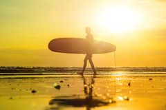 Vacation Silhouette Of A Surfer Carrying His Surf Board Home At Sunset With Copy Space.  Royalty Free Stock Photos
