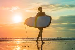 Vacation Silhouette Of A Surfer Carrying His Surf Board Home At. Sunset With Copy Space Stock Photography