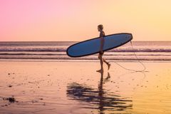Vacation Silhouette Of A Surfer Carrying His Surf Board Home At. Sunset With Copy Space Stock Images