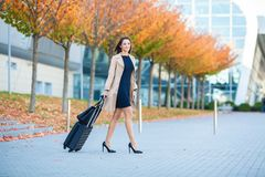 Vacation. Smiling female passenger proceeding to exit gate pulling suitcase through airport concourse.  royalty free stock photography