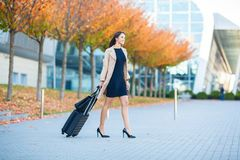 Vacation. Smiling female passenger proceeding to exit gate pulling suitcase through airport concourse.  stock image